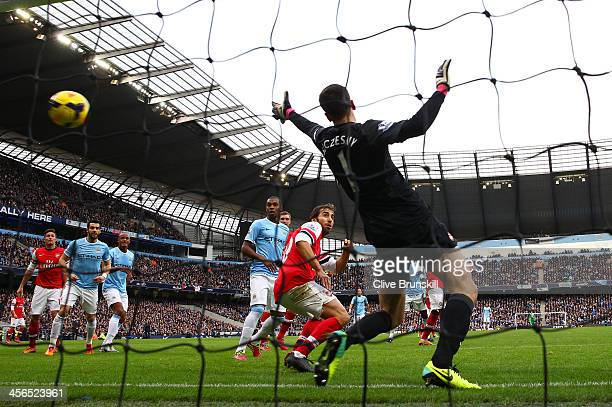 Wojciech Szczesny of Arsenal can't stop Sergio Aguero of Manchester City scoring their first goal during the Barclays Premier League match between...