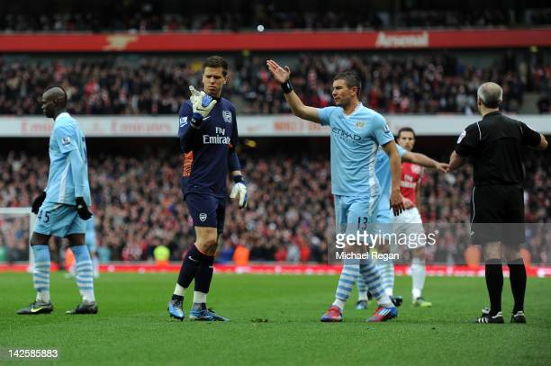 Wojciech Szczesny of Arsenal looks at a bottle of beer that was thrown onto the pitch during the Barclays Premier League match between Arsenal and...