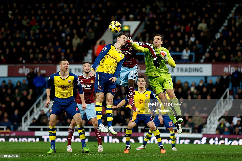 Wojciech Szczesny of Arsenal punches the ball clear from Enner Valencia of West Ham during the Barclays Premier League match between West Ham United and Arsenal at Boleyn Ground on December 28, 2014 in London, England.