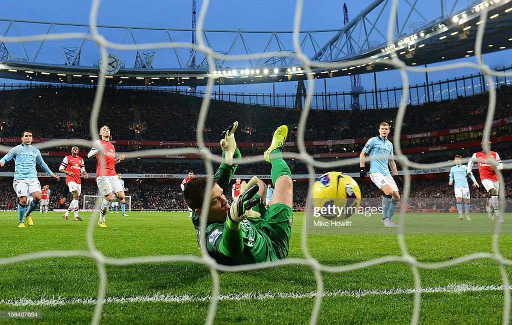 Wojciech Szczesny of Arsenal saves a penalty from Edin Dzeko of Manchester City (R) during the Barclays Premier League match between Arsenal and Manchester City at Emirates Stadium on January 13, 2013 in London, England.