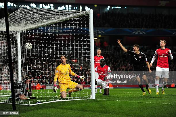 Wojciech Szczesny of Arsenal scrambles in vain to prevent the ball crossing the line as goalscorer Mario Mandzukic of Bayern Muenchen watches from...