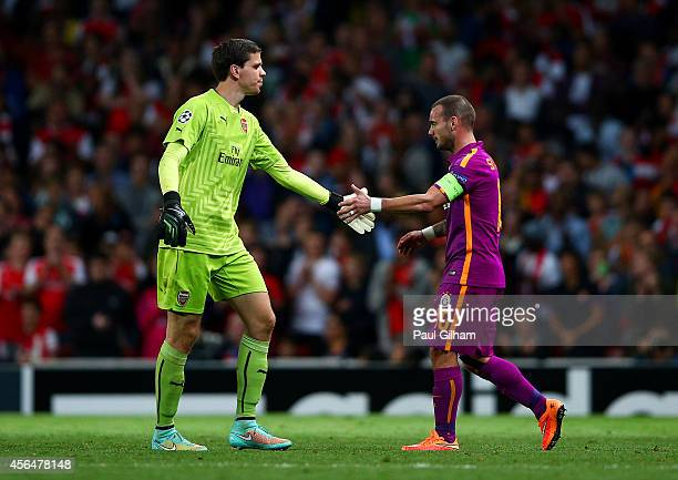 Wojciech Szczesny of Arsenal taps hands with Wesley Sneijder of Galatasaray AS as he walks off the pitch after receiving a red card during the UEFA...
