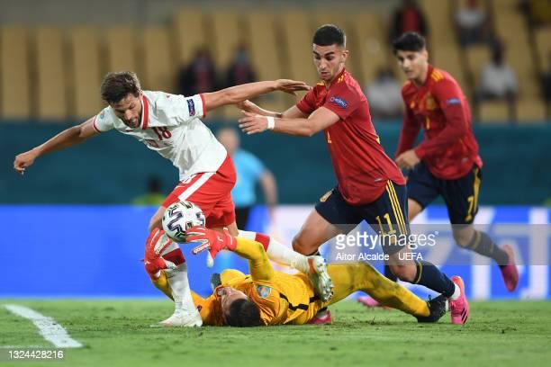 Wojciech Szczesny of Poland makes a save whilst under pressure from team mate Bartosz Bereszynski and Ferran Torres of Spain during the UEFA Euro...