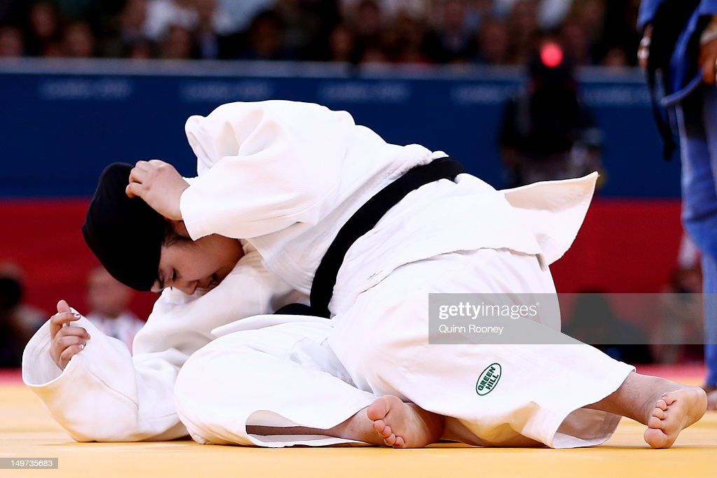 Wojdan Shaherkani of Saudi Arabia (white) adjusts her hijab while competing with Melissa Mojica of the United States in the Women's +78 kg Judo Women's +78 kg Judo on Day 7 of the London 2012 Olympic Games at ExCeL on August 3, 2012 in London, England.