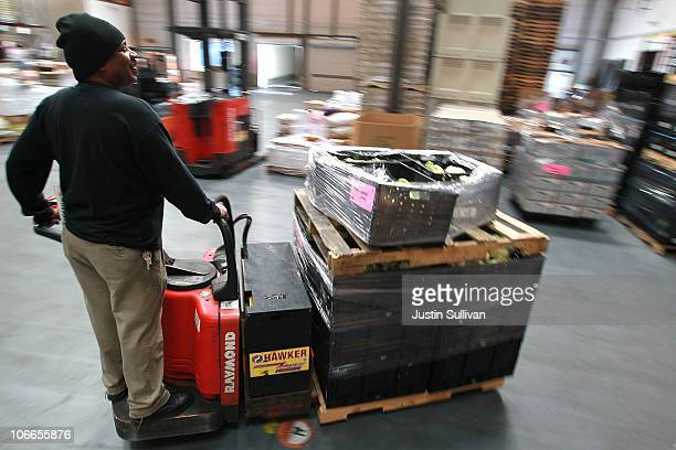 A woker uses a forklift to move a pallet of food in the warehouse at the San Francisco Food Bank on November 9 2010 in San Francisco California With...