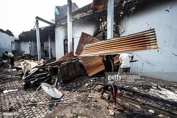 Wokers clean the prison office after a riot in Lhokseumawe on February 16 2014 At least three inmates were injured and a jail officer was burnt down...