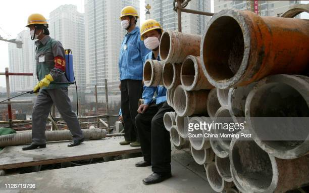 Wokers on the Shuntian Tong construction site in Changping County, north of Beijing disinfect the worksite to control the SARS virus. Many projects...