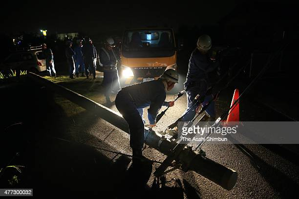Wokers remove an electric pole fallen by strong winds on June 15, 2015 in Isesaki, Gunma, Japan. The blustery winds overturned cars and two injured,...