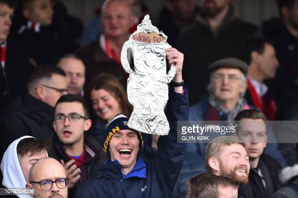 A Woking fan holds up a homemade tinfoil FA Cup in the crowd during the English FA Cup third round football match between Woking and Watford at...