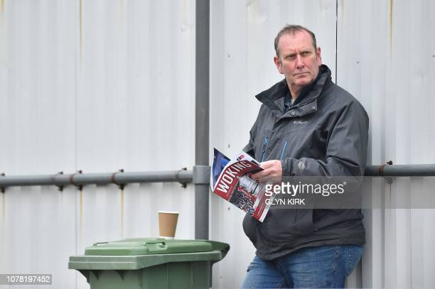 A Woking fan reads a matchday programme ahead of the English FA Cup third round football match between Woking and Watford at Kingsfield Stadium in...