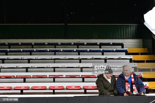 Wokings wait in the stands ahead of the English FA Cup third round football match between Woking and Watford at Kingsfield Stadium in Woking, west of...