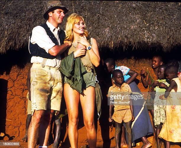 """Wolfgang Fierek, Bea Fiedler, Kinofilm, """"Das verrückte Strandhotel"""", Kenia, Eingeborene, Hütte, Hut,"""