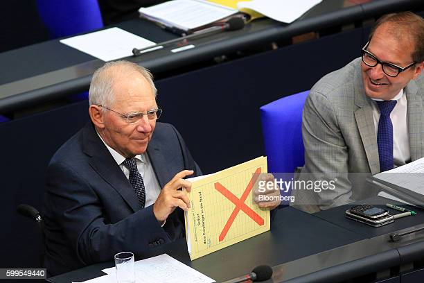Wolfgang Schaeuble Germany's finance minister holds a document as Alexander Dobrindt Germany's transport minister reacts as Germany's 2017 budget is...