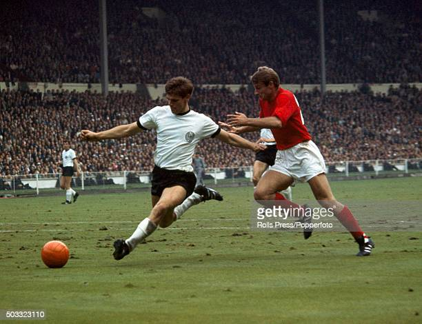 Wolfgang Weber of West Germany intercepts the ball under pressure from England striker Roger Hunt during the FIFA World Cup Final between England and...