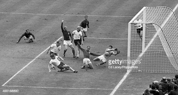 Wolfgang Weber of West Germany scores past England goalkeeper Gordon Banks to level the score at 22 in the last minute of normal time during the...