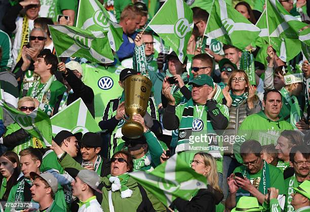 Wolfsburg fan shows his support holding a replica of the DFB Cup trophy ahead of the DFB Cup Final match between Borussia Dortmund and VfL Wolfsburg...