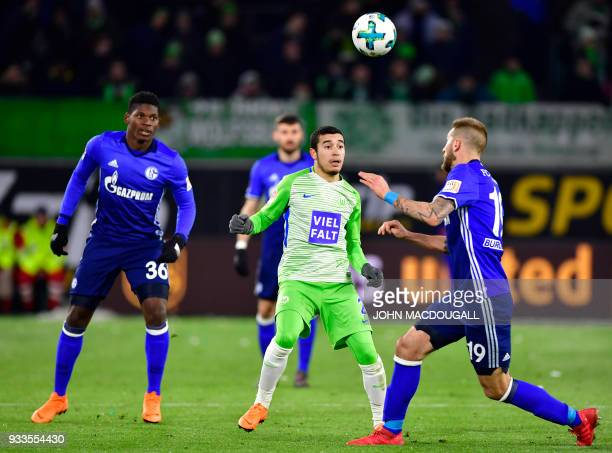 Wolfsburg's Brazilian defender William vies with Schalke's Swiss forward Breel Embolo and Schalke's Austrian forward Guido Burgstaller during the...