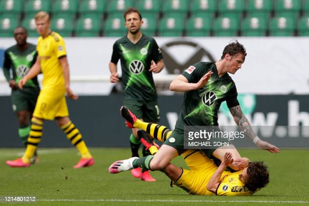 Wolfsburg's Dutch forward Wout Weghorst falls down on Dortmund's Danish midfielder Thomas Delaney during the German first division Bundesliga...