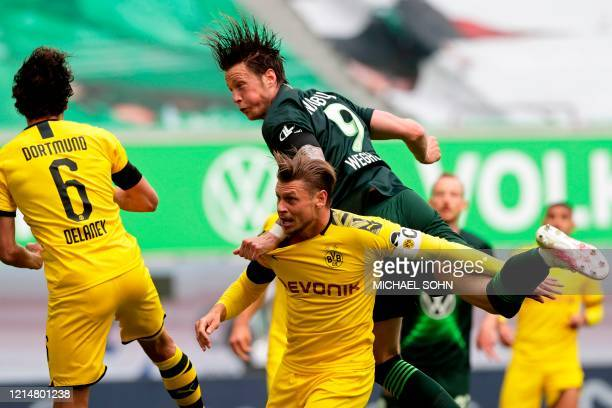 Wolfsburg's Dutch forward Wout Weghorst pulls on the shirt of Dortmund's Polish defender Lukasz Piszczek during the German first division Bundesliga...