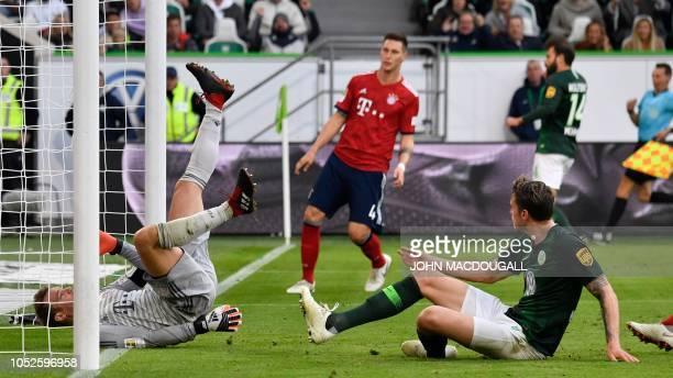 Wolfsburg's Dutch forward Wout Weghorst scores past Bayern Munich's German goalkeeper Manuel Neuer during the German First division Bundesliga...