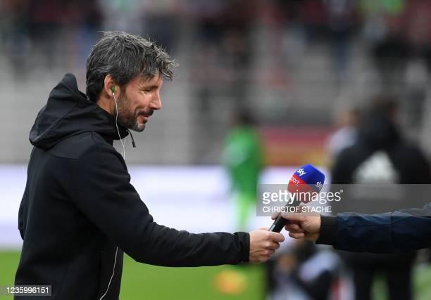 Wolfsburg's Dutch head coach Mark van Bommel returns the microphone after an interview prior the German first division Bundesliga match between Union...