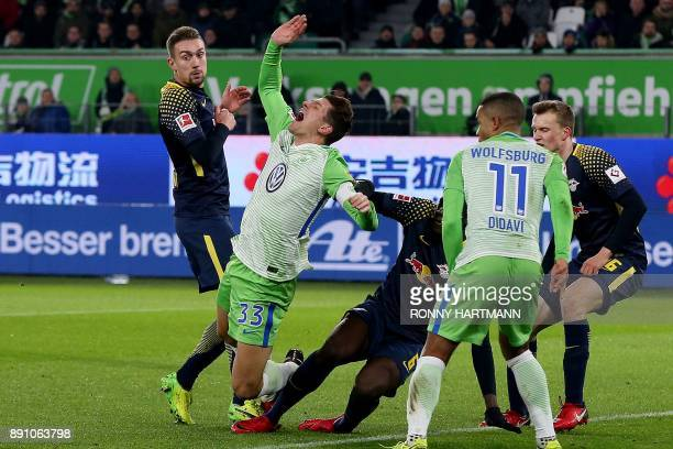 Wolfsburg's forward Mario Gomez is tackled by French defender Ibrahima Konate as Leipzig's Austrian midfielder Stefan Ilsanker looks on during the...