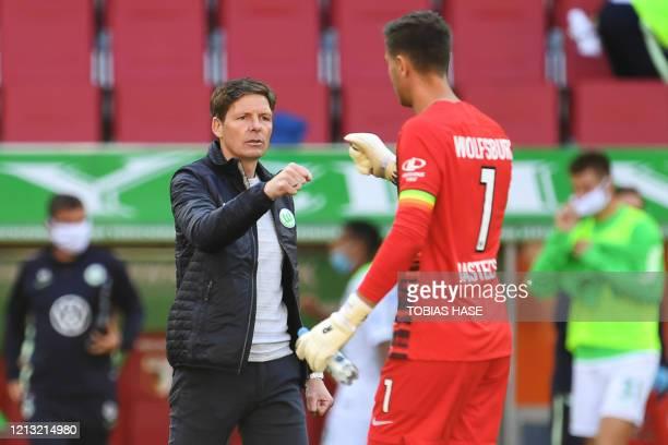 Wolfsburg's German head coach Oliver Glasner celebrates with Wolfsburg's Belgian goalkeeper Koen Casteels after winning the German first division...