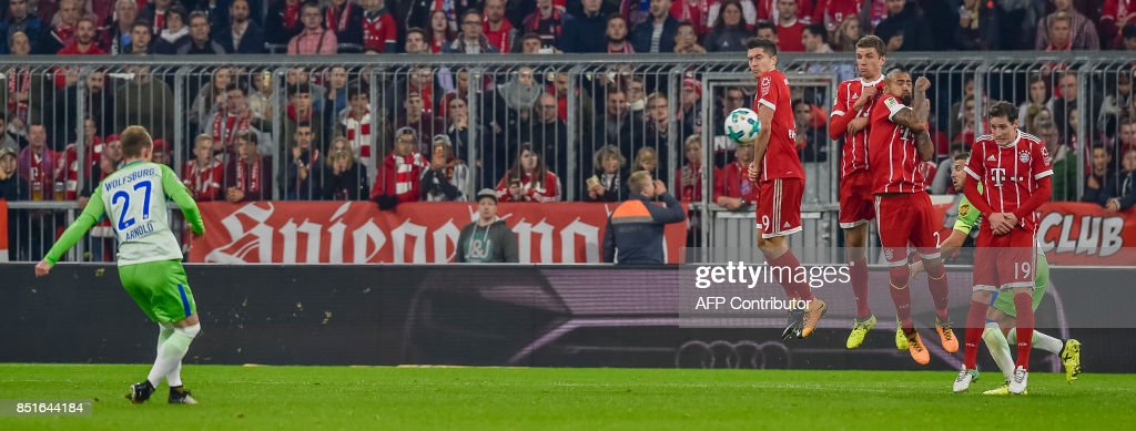 Wolfsburg's German midfielder Maximilian Arnold (L) scores past the Bayern wall during the German First division Bundesliga football match FC Bayern Munich vs VfL Wolfsburg in Munich, southern Germany, on September 22, 2017. / AFP PHOTO / Guenter