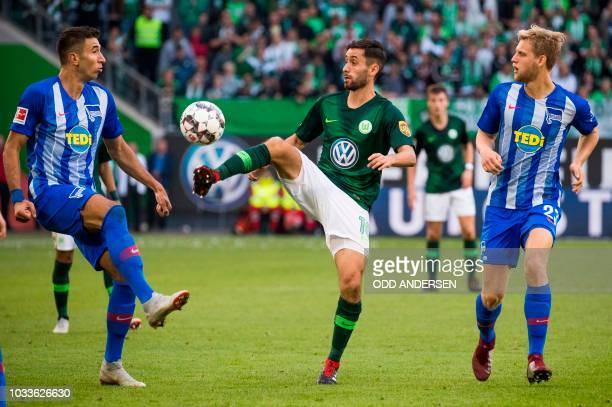 Wolfsburg's German midfielder Yunus Malli Berlin's German midfielder Arne Maier and Berlin's Serbian midfielder Marko Grujic vie for the ball during...