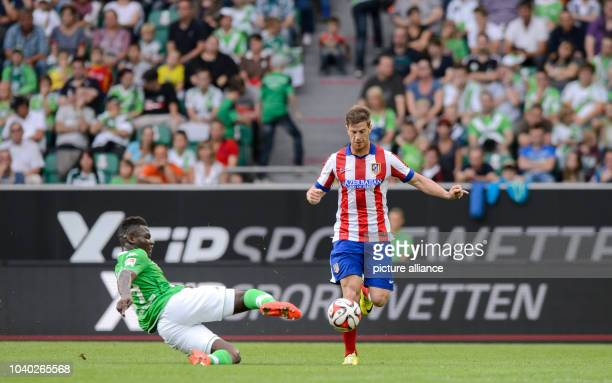 Wolfsburg's Junior Malanda and Madrid's Cristian Ansaldi in action during the soccer test match between VfL Wolfsburg and Atletico Madrid at...