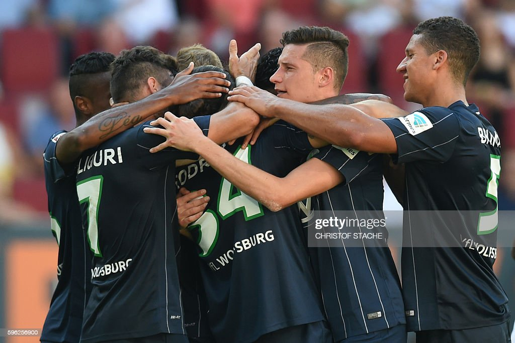 Wolfsburg's players celebrate after scoring during the German first division Bundesliga football match of FC Augsburg vs VfL Wolfsburg in Augsburg, southern Germany, on August 27, 2016. / AFP / CHRISTOF