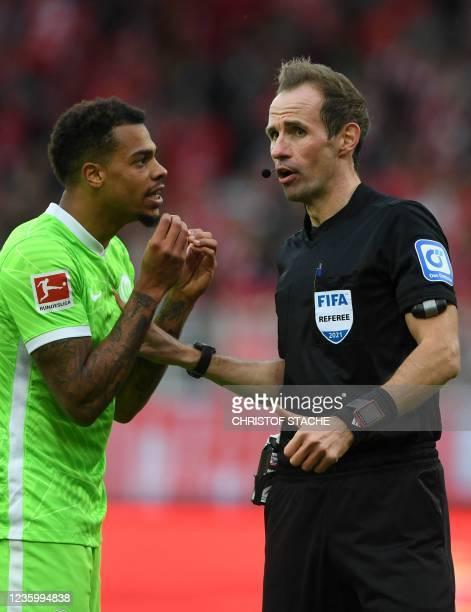 Wolfsburg's striker Lukas Nmecha talks with the referee Sascha Stegemann during the German first division Bundesliga match between Union Berlin and...