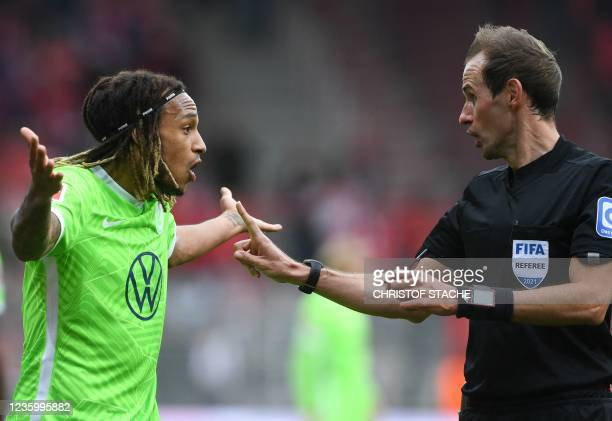 Wolfsburg's Swiss defender Kevin Mbabu gestures next to referee Sascha Stegemann during the German first division Bundesliga match between Union...