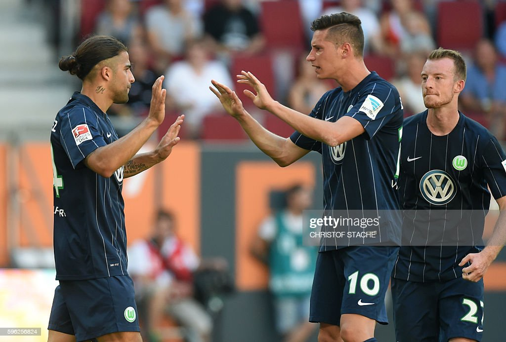 Wolfsburg's Swiss defender Ricardo Rodriguez, Wolfsburg's midfielder Julian Draxler and Wolfsburg's midfielder Maximilian Arnold celebrate after scoring during the German first division Bundesliga football match of FC Augsburg vs VfL Wolfsburg in Augsburg, southern Germany, on August 27, 2016. / AFP / CHRISTOF