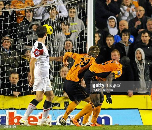 Wolverhampton Wanderers' Cameroonian defender George Elokobi and teammate Irish striker Kevin Doyle watch the ball hit the back of the net for their...