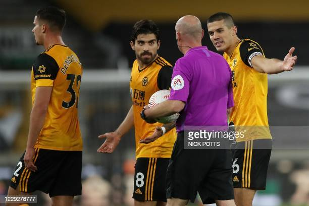 Wolverhampton Wanderers' English defender Conor Coady remonstrates with Referee Lee Mason after he blew the whistle to end the first half as...