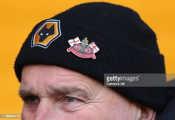 Wolverhampton Wanderers fan is seen wearing a hat with a 'Lest We Forget' badge in mark of Armistice Day prior to the Premier League match between...