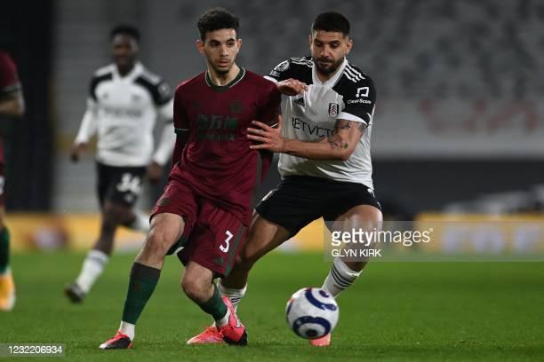 Wolverhampton Wanderers' French defender Rayan Aït-Nouri vies with Fulham's Serbian striker Aleksandar Mitrovic during the English Premier League...