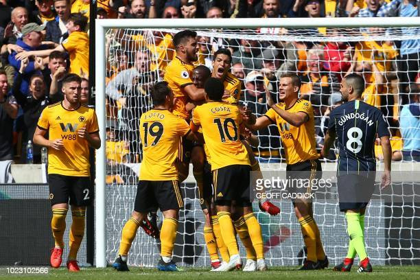 Wolverhampton Wanderers' French defender Willy Boly celebrates with team-mates after scoring the opening goal during the English Premier League...