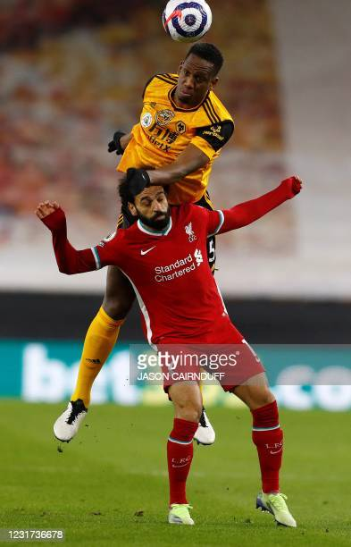 Wolverhampton Wanderers' French defender Willy Boly jumps above Liverpool's Egyptian midfielder Mohamed Salah to header the ball during the English...