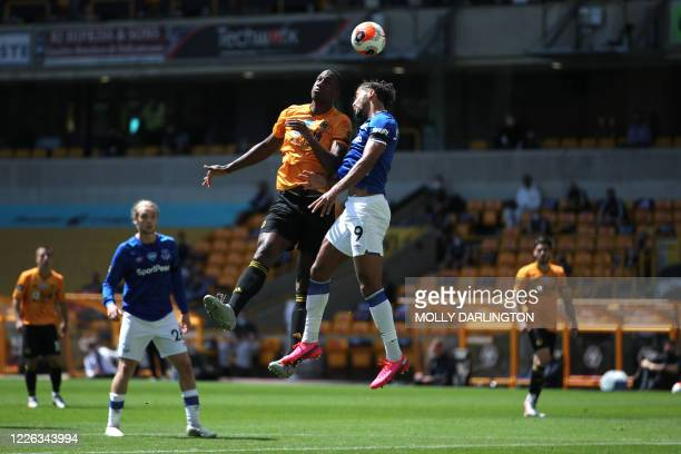 Wolverhampton Wanderers' French defender Willy Boly jumps for a header with Everton's English striker Dominic Calvert-Lewin during the English...