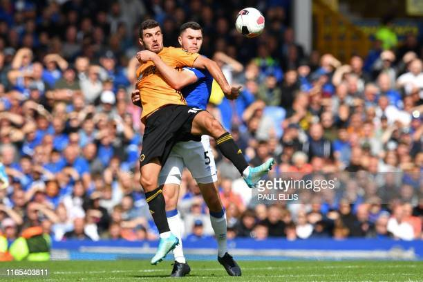 Wolverhampton Wanderers' Italian striker Patrick Cutrone is fouled by Everton's English defender Michael Keane during the English Premier League...