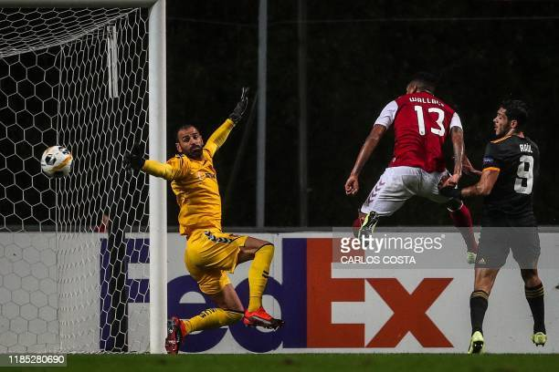 Wolverhampton Wanderers' Mexican forward Raul Jimenez scores a goal next to Sporting Braga's Brazilian defender Wallace and Sporting Braga's...