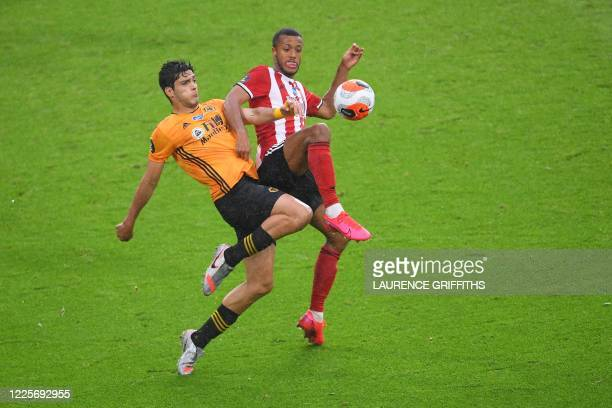 Wolverhampton Wanderers' Mexican striker Raul Jimenez vies Sheffield United's Dutch striker Richairo Zivkovic with during the English Premier League...