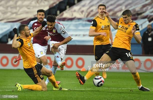 Wolverhampton Wanderers' Moroccan midfielder Romain Saiss comes across to block a shot from Aston Villa's English striker Ollie Watkins as...