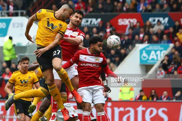 Wolverhampton Wanderers' Moroccan midfielder Romain Saiss jumps to head the ball during the English FA Cup fifth round football match between Bristol...
