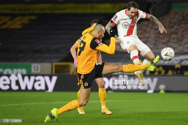 Wolverhampton Wanderers' Moroccan midfielder Romain Saiss stretches out a leg to block a shot from Southampton's English striker Danny Ings during...