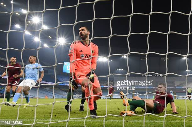 Wolverhampton Wanderers' Portuguese goalkeeper Rui Patricio reacts as Wolverhampton Wanderers' Belgian midfielder Leander Dendoncker scores an own...