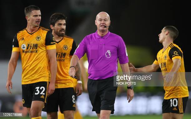 Wolverhampton Wanderers' Portuguese midfielder Daniel Podence remonstrates with Referee Lee Mason after he blew the whistle to end the first half as...