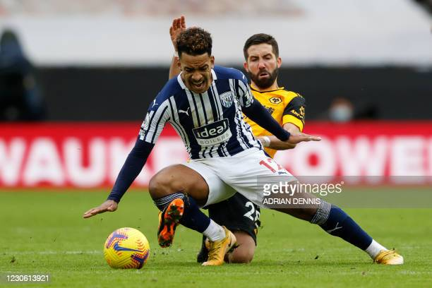 Wolverhampton Wanderers' Portuguese midfielder Joao Moutinho tackles West Bromwich Albion's Brazilian midfielder Matheus Pereira during the English...